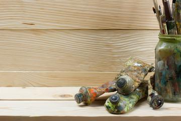 Artistic, artist, art. Used artist paintbrushes mastehin on wood background.