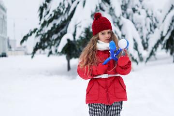Portrait of lovely little girl holding snowball maker