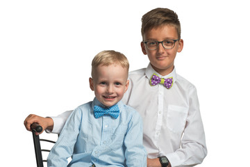 Two boys brothers sitting on a chair in shirt and butterfly isolated on white background