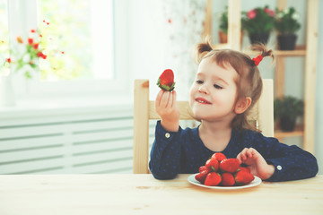 happy child girl eats strawberries in summer home kitchen