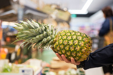 Close-up of woman's hand holding a pineapple in a supermarket