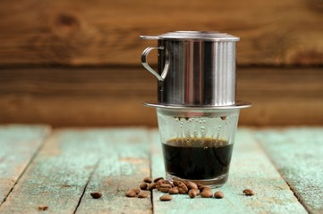 Vietnamese black coffee brewed in French drip filter on turquois