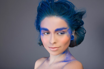 Beautiful woman with bright creative make up in blue