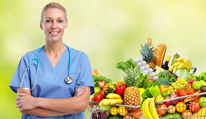Wall Mural - Smiling nurse near shopping cart with food.