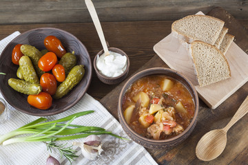 Traditional ukrainian vegetable soup - borsch, marinated tomatoes and cucumbers, sour cream, sliced bread, herbs and garlic at dark wooden table.