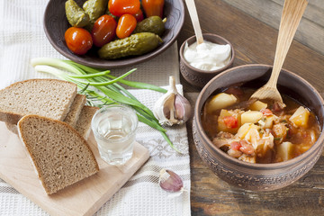 Traditional ukrainian vegetable soup - borsch, marinated tomatoes and cucumbers, sour cream, sliced bread, herbs and garlic, vodka in glass cup at dark wooden table.