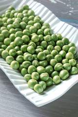 Fresh Peeled Green Peas in a white plate on a wooden background