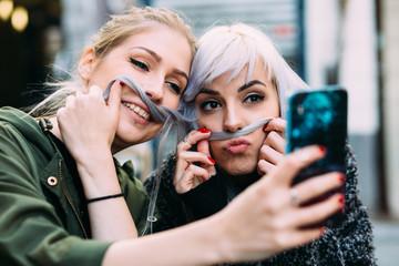 Silly young women best friends taking a selfie