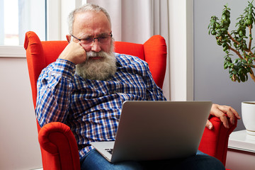 man in glasses looking at laptop