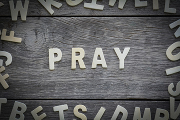The word pray on the wooden floor