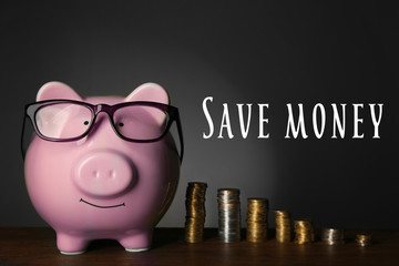 Piggy bank with glasses and coins on table, gray background