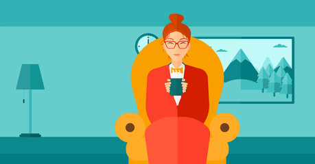 Woman sitting in chair with cup of tea.