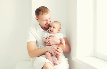 Happy smiling young father and baby at home in white room near w