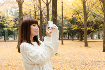 写真を撮りながら公園を散歩している女性