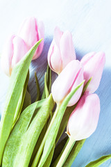 Pink pastel tulips on wooden board