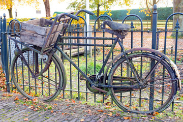 Old fashioned dutch bike against a fence