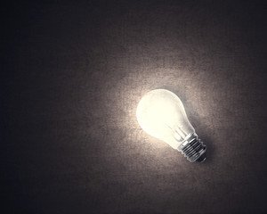 Lighting bulb with wooden background glowing in dark
