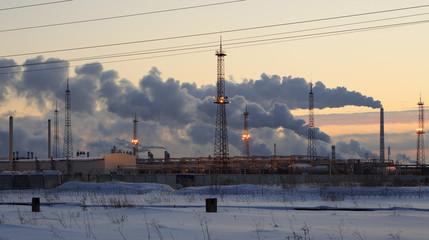 Refinery at sunset sky background. Frosty snowy winter evening.
