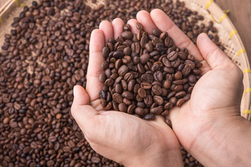 Coffee beans in hand by barista, background is a coffee beans in the bamboo basket