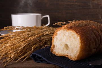 A bread and coffee with a soften light of morning background is texture of gain and wooden table, coffee concept