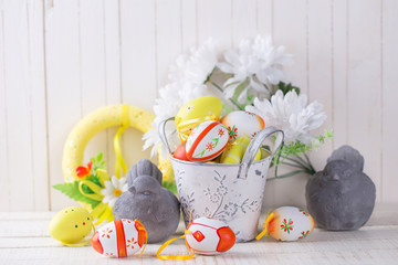 Colorful easter eggs and decorative birds on white  wooden backg