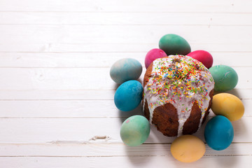 Colorful Easter cake and Easter eggs  on white wooden background