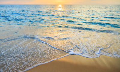 Blue sea and golden sand with sunset background