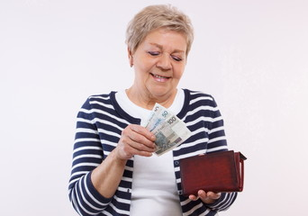 Happy senior female holding wallet with polish currency money, concept of financial security in old age