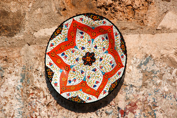 Painted ceramic plate with bright Oriental pattern on a stone wall