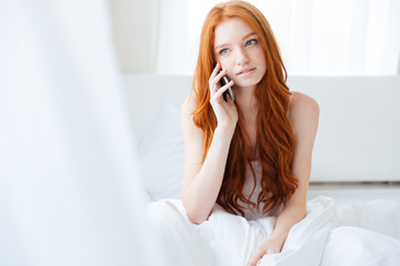 Beautiful woman talking on cell phone in bed