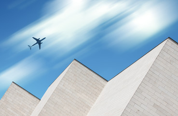 Airplane flying over modern white brick building with motion blur clouds in the background