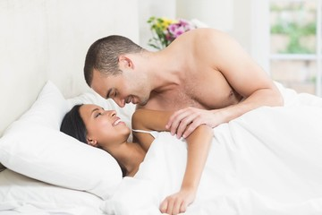 Smiling couple embracing in the bed