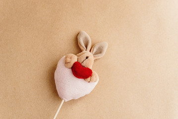 unique simple hand made bunny with heart on craft background, va