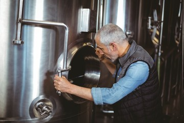Brewer checking large vats