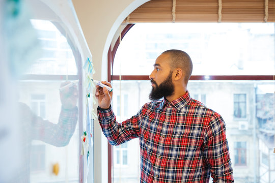 African man with beard standing and writing on whiteboard