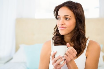 Happy woman holding cup of coffee while sitting on bed