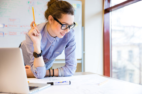 Happy woman working with blueprint near the window in office