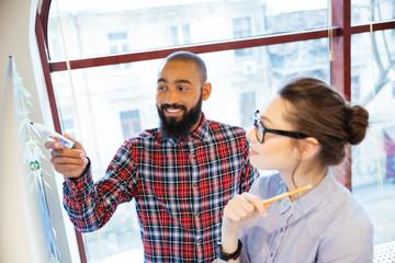 Pretty woman and african man preparing for presentation near whiteboard