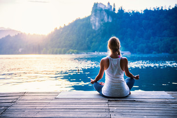 Photo sur Plexiglas Ecole de Yoga Yoga lotus. Young woman doing yoga by the lake, sitting in lotus.