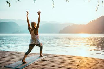 Yoga Sun Salutation. Young woman doing yoga by the lake at sunset, saluting to the sun.