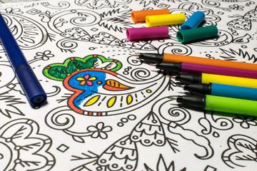 Trend für Stressabbau - Ausmalbuch für Erwachsene - Stifte in verschiedenen Farben auf einem Blatt Papier mit Muster zum Ausmalen - Nahaufnahme von verschieden farbigen Stiften