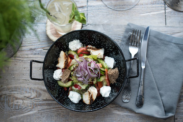 Cucumber salad, toast, onion, tomato and cheese on a plate in the form of a frying pan