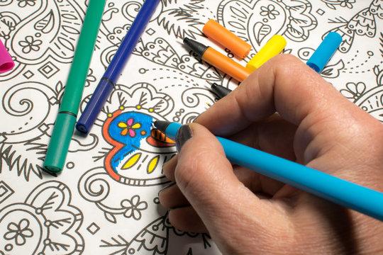 Trend für Stressabbau - Ausmalbuch für Erwachsene - Stifte in verschiedenen Farben auf einem Blatt Papier mit Muster zum Ausmalen - Hand in Nahaufnahme