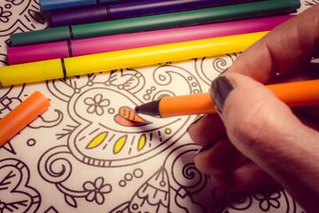 Trend für Stressabbau - Ausmalbuch für Erwachsene - Filzstifte und Hand in Nahaufnahme beim Zeichnen auf einem Blatt Papier mit Muster zum Ausmalen - Retro Stil