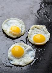 Fried eggs on black background