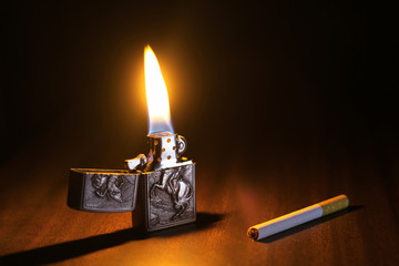 A burning lighter and cigarette on a wooden floor