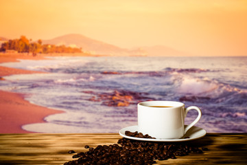 Coffee beans and coffee in cup on wooden table opposite a blurre