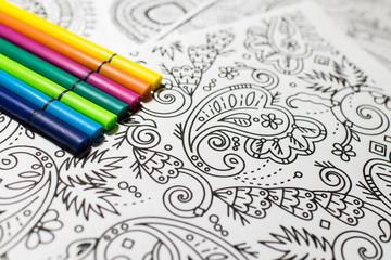Trend für Stressabbau - Ausmalbuch für Erwachsene - Filzstifte in verschiedenen Farben auf einem Blatt Papier mit Muster zum Ausmalen . Nahaufnahme