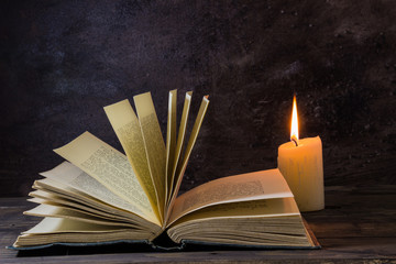 old book by candlight with fanning pages