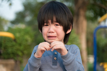 asian boy  crying in the park